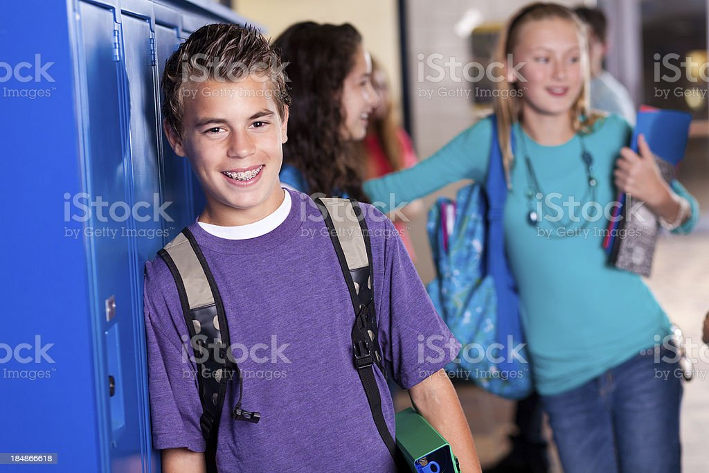 Young student at school lockers with friends stock photo