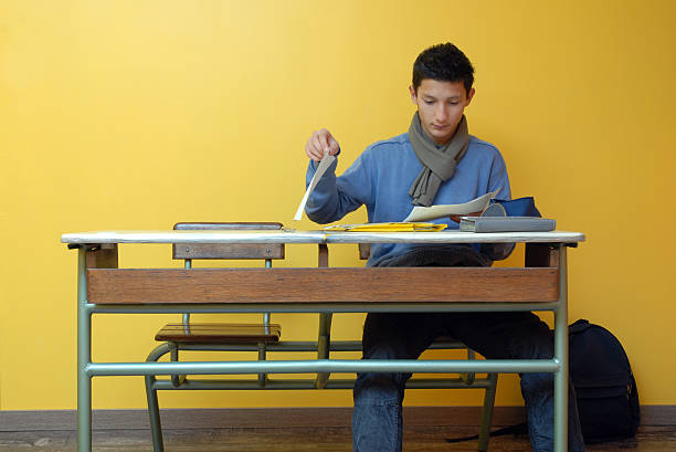 young student behind his desk stock photo