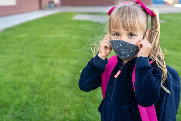 jeune fille caucasienne d'étudiant utilisant le masque protecteur de coton pour l'école. retour à l'école, réouverture, nouvelle vie - masque enfant photos et images de collection