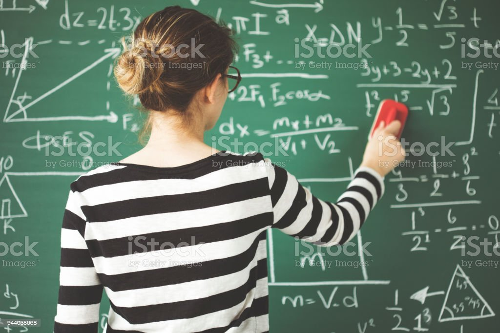 Young student cleaning green chalkboard with duster  in classroom stock photo
