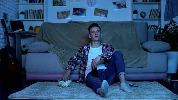 young student drinking beer and eating popcorn watching tv show, weekend leisure - divano procrastinazione foto e immagini stock