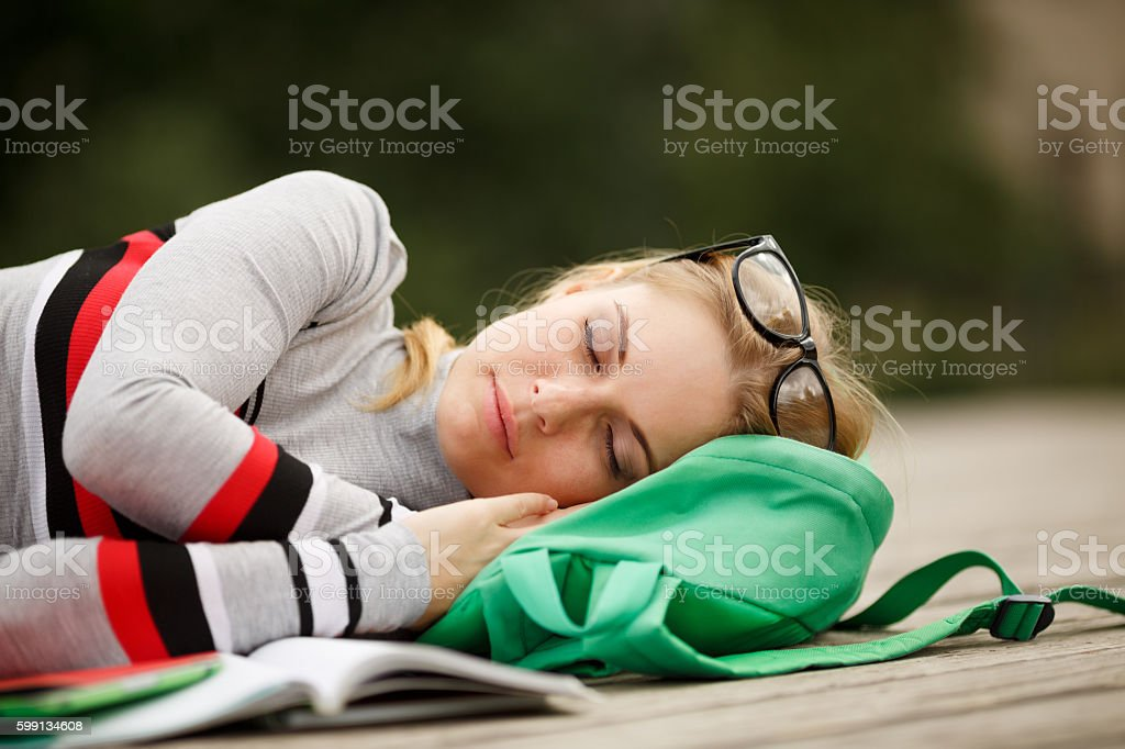 young student fell asleep with book on wooden floor stock photo