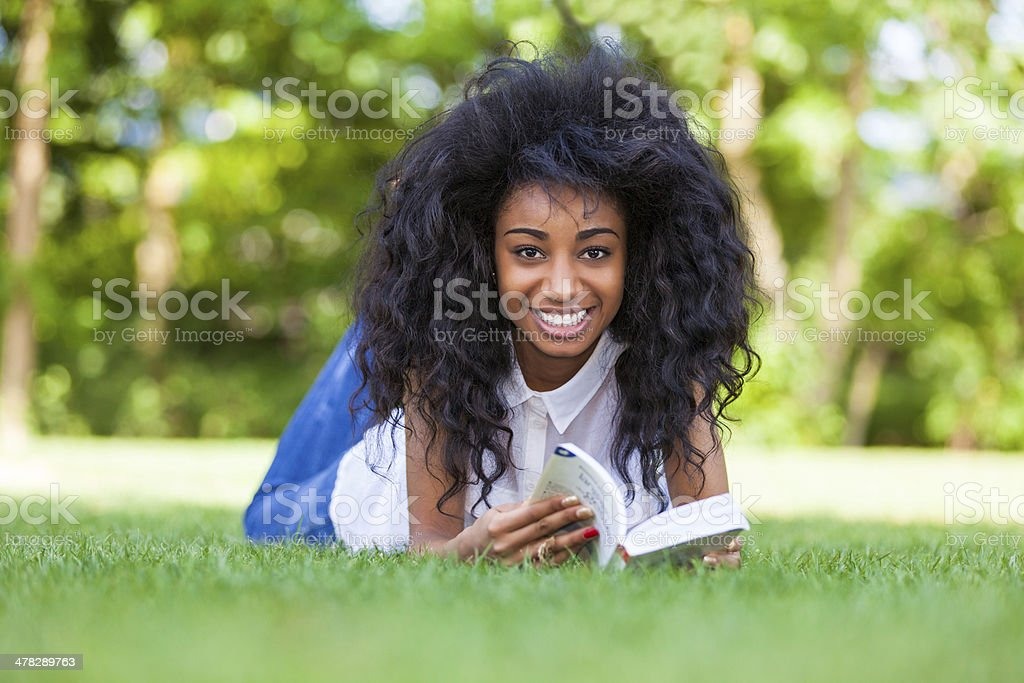 Young student girl reading a book in the school park royalty-free stock photo