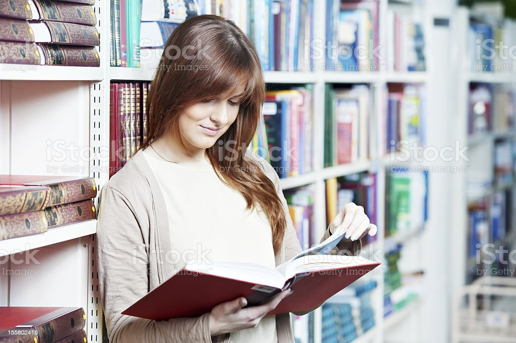 young student girl reading book in library stock photo