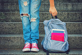 Young student girl with backpack staying on the stairs - back to school concept
