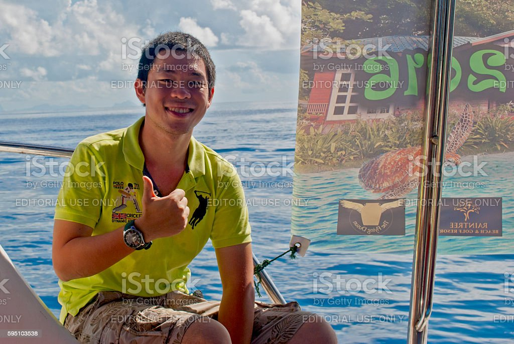Young student giving the thumbs up on a catamaran stock photo