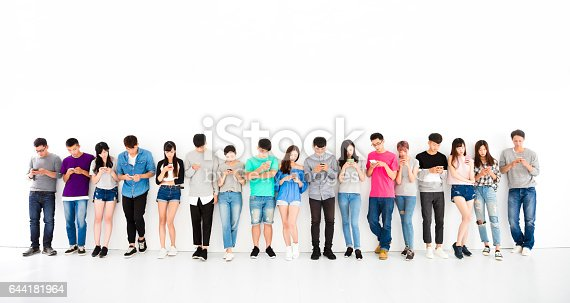 istock young student Group watching smart phone 644181964