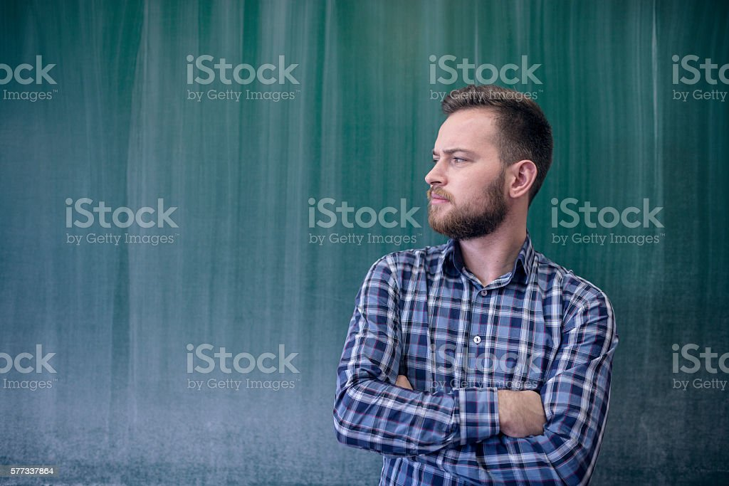 Young Student in Front of Blackboard Looking at Copy Space stock photo