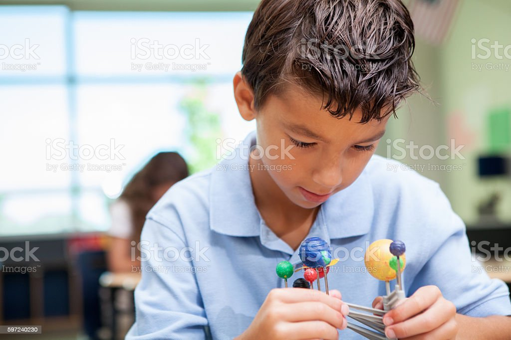 Young student in science class studying solar system model stock photo
