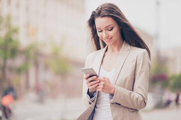 jonge student is browsen op haar pda terwijl met een veer lopen in de stad buiten, in een formele outfit, glimlachen, gonna ontmoet vriend, wind speelt met haar haren - business woman phone stockfoto's en -beelden