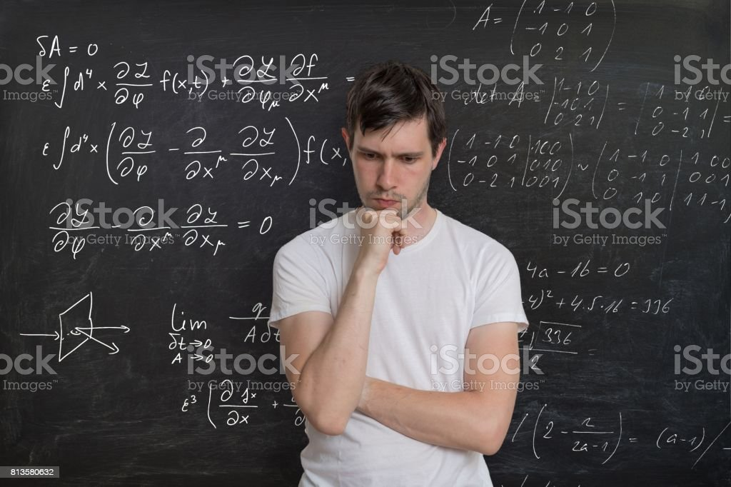 Young student is solving math exam. Mathematics formular on blackboard in background. stock photo