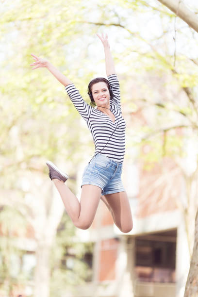 Young student jumping in front of a camera outdoors stock photo