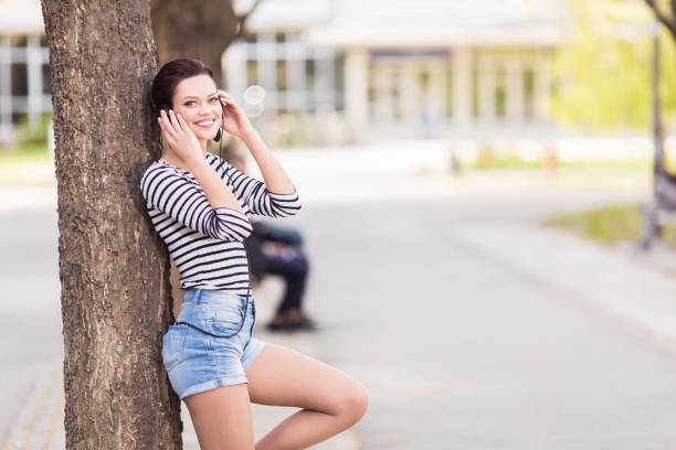 Young student leaning on a tree outdoors stock photo
