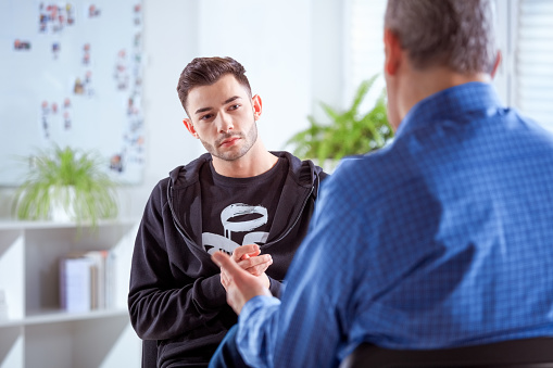Young Student Listening To Therapist In University Stock Photo - Download Image Now