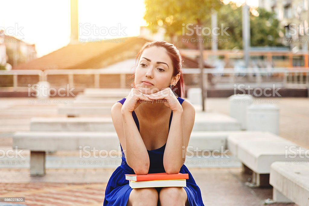 young student looks bored while waiting for someone foto royalty-free