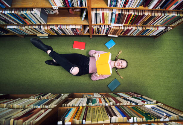 young student lying on the floor in library and reading book. - librerie foto e immagini stock