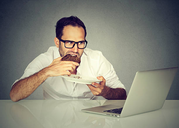 young student man eating while working on laptop - nerd boy eating stock photos and pictures