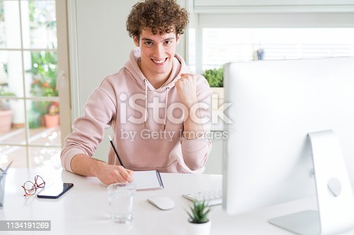 1175468850istockphoto Young student man using computer and studying writing on notebook screaming proud and celebrating victory and success very excited, cheering emotion 1134191269