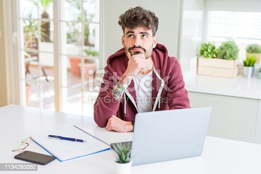 istock Young student man using computer laptop and notebook serious face thinking about question, very confused idea 1134263352