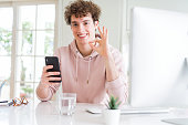 Young student man using smartphone and computer doing ok sign with fingers, excellent symbol