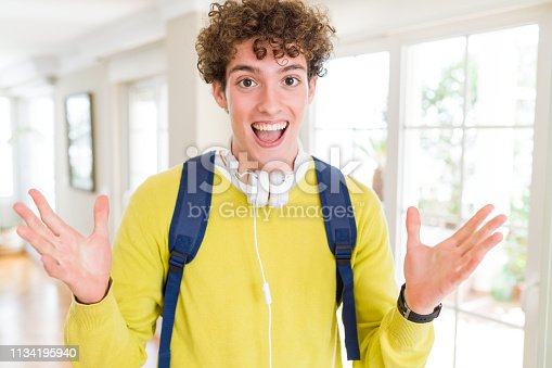 1175468850istockphoto Young student man wearing headphones and backpack celebrating crazy and amazed for success with arms raised and open eyes screaming excited. Winner concept 1134195940