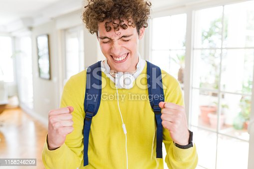 1175468850istockphoto Young student man wearing headphones and backpack excited for success with arms raised celebrating victory smiling. Winner concept. 1158246209