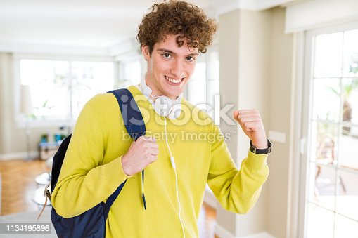 1175468850istockphoto Young student man wearing headphones and backpack screaming proud and celebrating victory and success very excited, cheering emotion 1134195896