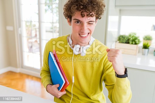 1175468850istockphoto Young student man wearing headphones and holding notebooks screaming proud and celebrating victory and success very excited, cheering emotion 1162394457