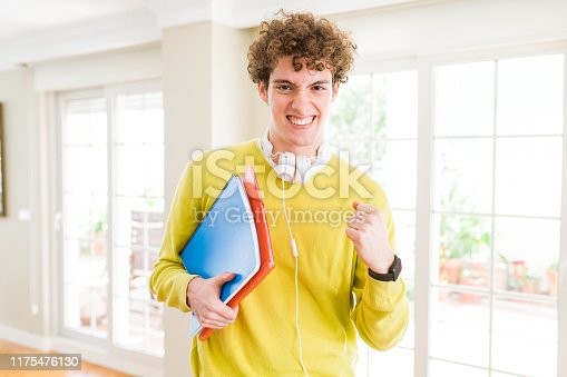 1175468850istockphoto Young student man wearing headphones and holding notebooks screaming proud and celebrating victory and success very excited, cheering emotion 1175476130