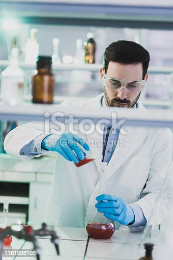 Male microbiologist working with chemical substances in laboratory.