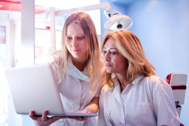 ung student på tandvård eller sjuksköterska och kvinnliga tandläkare titta på laptop grupp i tandläkarens. - two dentists talking bildbanksfoton och bilder