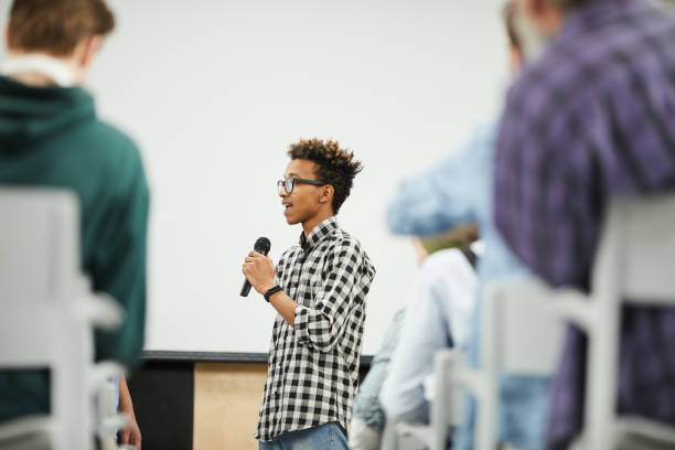 Young student presenting his startup project at conference Cheerful confident young black student with Afro hairstyle standing in convention center room and presenting his startup project at conference debate stock pictures, royalty-free photos & images