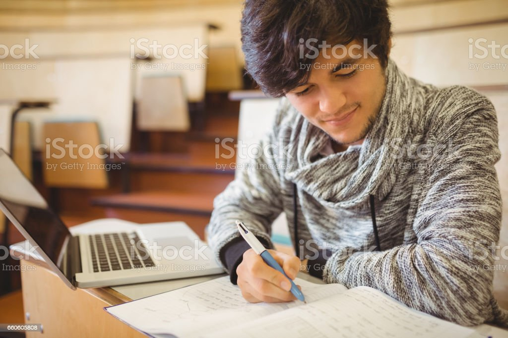 Young student sitting at a desk writing notes royalty-free stock photo