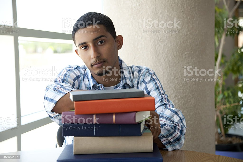 Young student sitting at table with pile of books royalty-free stock photo