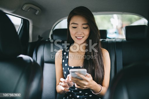 Young student sitting on the backseat of a taxi. She's checking her smartphone for the street name.
