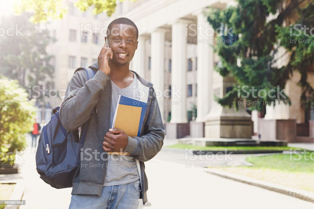 Young student talking on smartphone in the park royalty-free stock photo