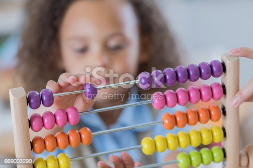istock Young student uses abacus at school 669003290