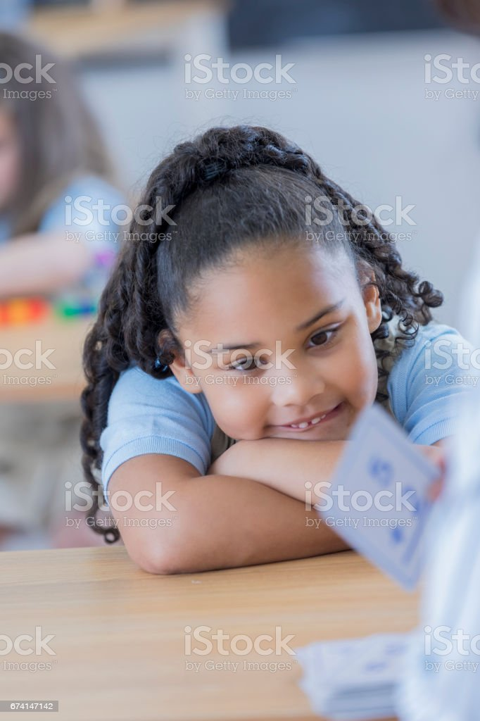 Cheerful young elementary student uses flashcards in class. Her...