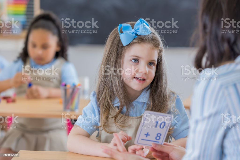 Young student uses flashcards in math class stock photo