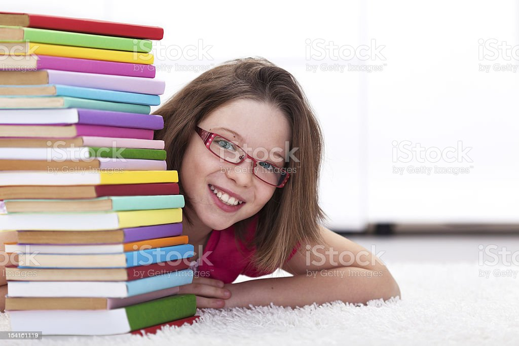 Young student with lots of books smiling stock photo