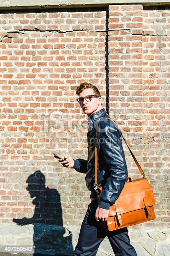 Young student walking with shoulder bag and smartphone