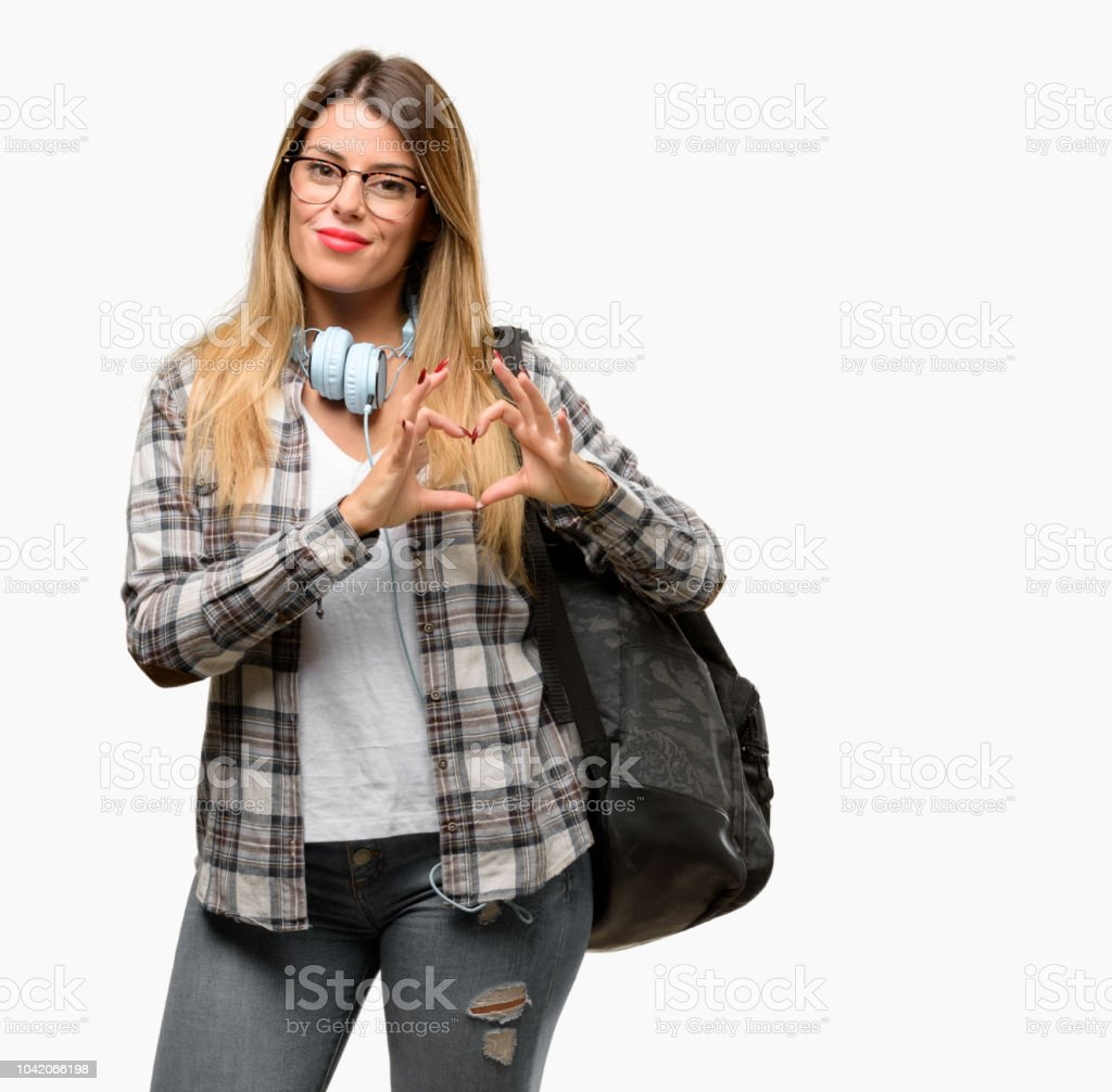 Young student woman with headphones and backpack happy showing love with hands in heart shape expressing healthy and marriage symbol stock photo