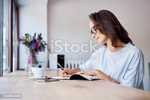 1183295518 istock photo Young student writing in notebook while having coffee in a cafe 1040944346