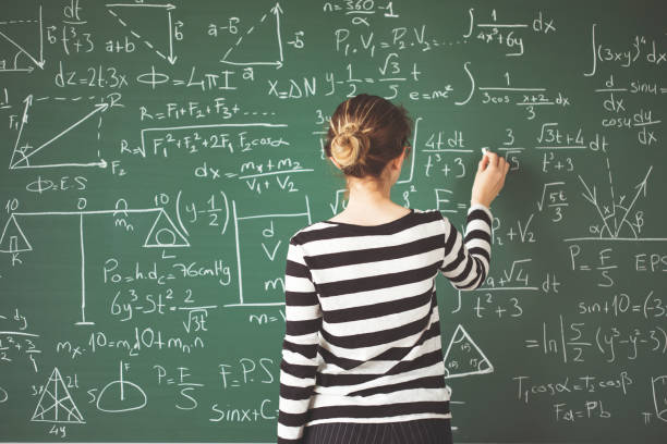 Young student writing with chalk on green chalk board in classroom stock photo