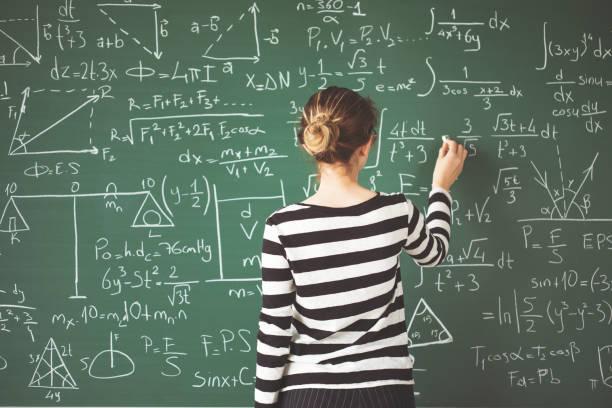 Jeune étudiant par écrit à la craie sur tableau de craie verte en salle de classe - Photo