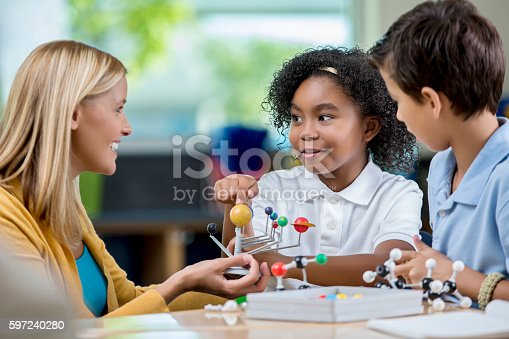 istock Young students and teacher in science class studying solar system 597240280