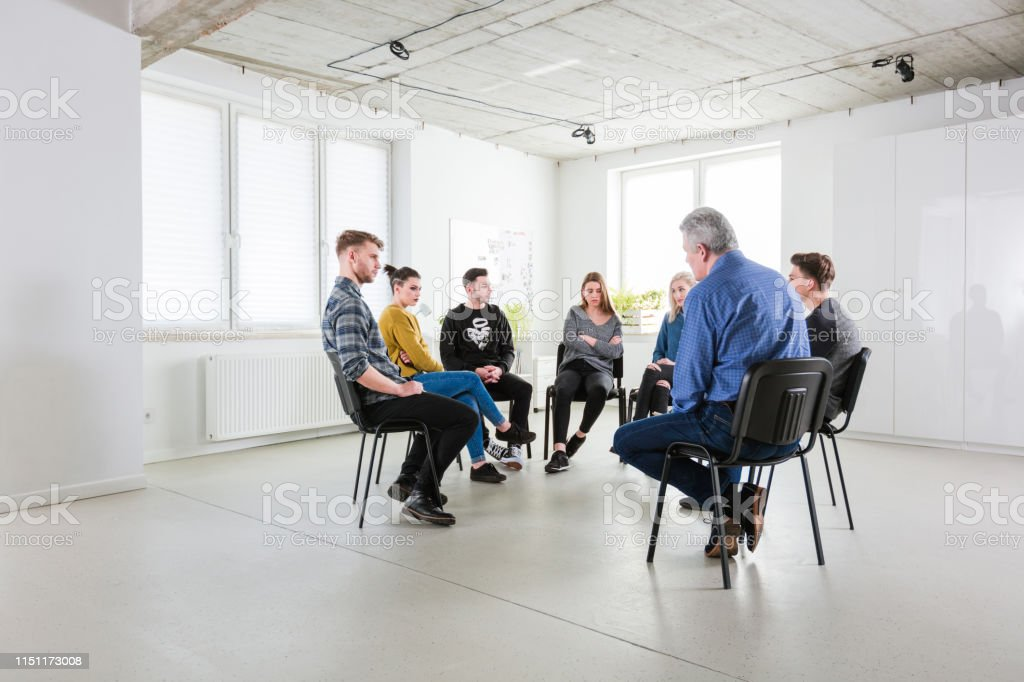 Young students and therapist sitting in meeting University students and therapist sitting during meeting. Mental health professional is with young men and women. They are in group therapy at lecture hall. 18-19 Years Stock Photo