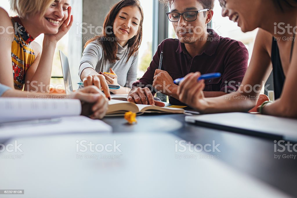 Young students collaborating on project in library stock photo