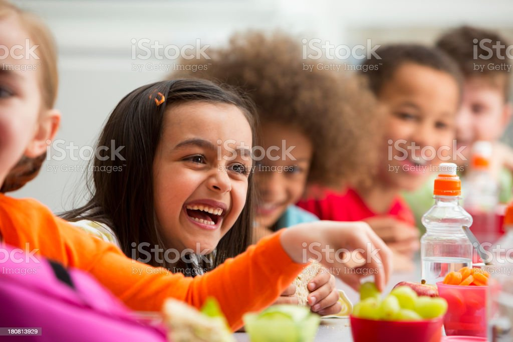 Young Students Enjoying Lunchtime At School stock photo