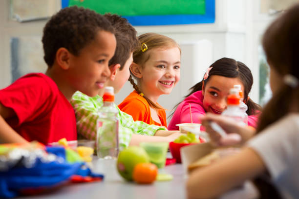 Young Students Enjoying Their Lunch At School stock photo